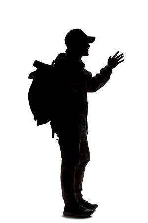 Silhouette of a man wearing a backpack looking like a traveler or hiker trekking. He is gesturing like he is talking or speaking