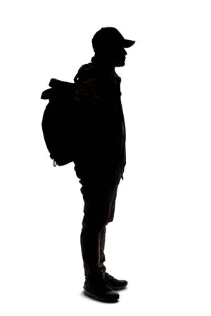 Silhouette of a man wearing a backpack looking like a traveler or hiker trekking.  He is patiently standing and waiting Foto de archivo