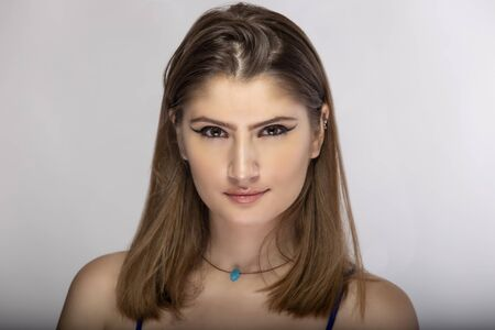 Beautiful female fashion model headshot posing with cosmetic eyeliner make up.  The close up portrait shows natural and simple style makeup