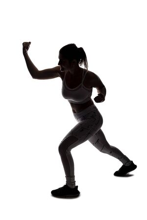 Fit young woman in a fighting stance wearing athletic sports wear and exercising by punching or practicing self defense. She is backlit as a silhouette on a white background Banco de Imagens