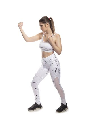 Fit young woman in a fighting stance wearing athletic sports wear and exercising by punching or practicing self defense.  She is isolated on a white background. Stockfoto