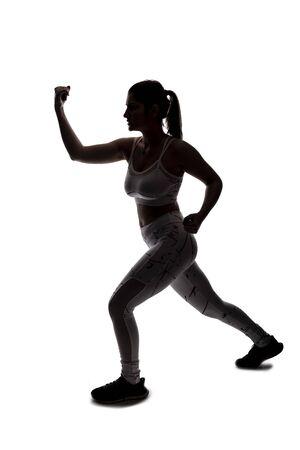 Colocar a una mujer joven en una posición de combate vistiendo ropa deportiva atlética y ejercitándose golpeando o practicando la autodefensa. Ella está retroiluminada como una silueta sobre un fondo blanco.