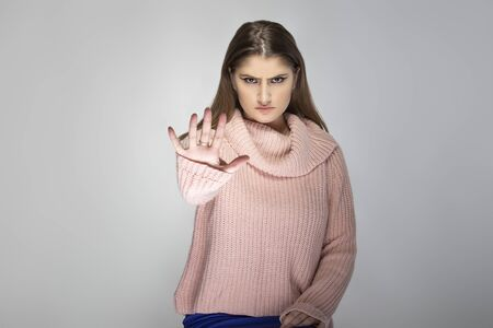 Close up portrait of a young Caucasian woman wearing a pink sweater on a grey background.  The model is holding hands up as a stop gesture