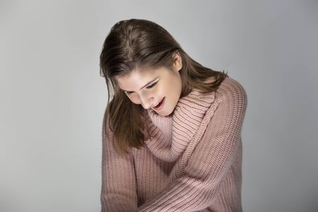 Close up portrait of a young Caucasian woman wearing a pink sweater on a grey background.  The model looks surprised and amazed