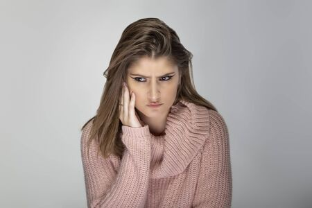 Close up portrait of a young Caucasian woman wearing a pink sweater on a grey background.  The model looks stressed out and worried