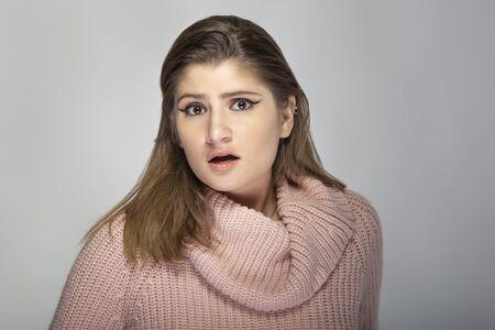 Primo piano ritratto di una giovane donna caucasica che indossa un maglione rosa su sfondo grigio. La modella sembra scioccata e spaventata Archivio Fotografico