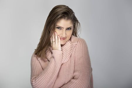 Close up portrait of a young Caucasian woman wearing a pink sweater on a grey background.  The model looks shy or embarrassed.