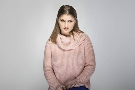 Close up portrait of a young Caucasian woman wearing a pink sweater on a grey background.  She looks disgusted or repulsed by something Stok Fotoğraf