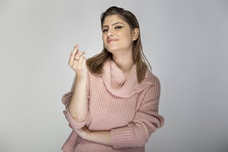 Close up portrait of a young Caucasian woman wearing a pink sweater on a grey background.  Her expressions is a money gesture