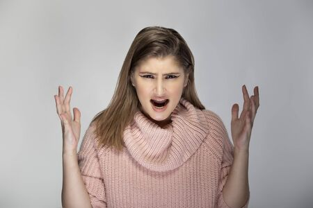 Close up portrait of a young Caucasian woman wearing a pink sweater on a grey background. She looks angry and in stress