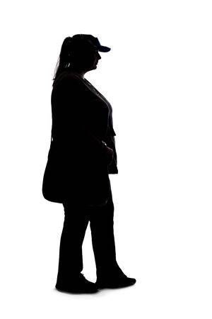 Silhouette of a curvy or plus size woman on a white background. She is unrecognizable and standing or waiting Stock Photo