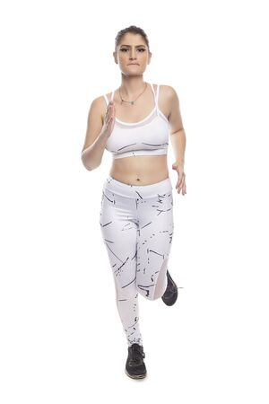 Woman wearing sports clothing running and isolated on white background for composites.  She is an active and fit Caucasian female who looks like she is exercising or practicing