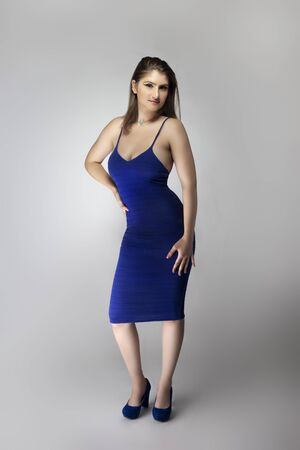 Catalog style studio shot of a Caucasian female fashion model wearing a navy or royal blue summer dress. She is posing to show trendy style of the outfit or clothing Imagens