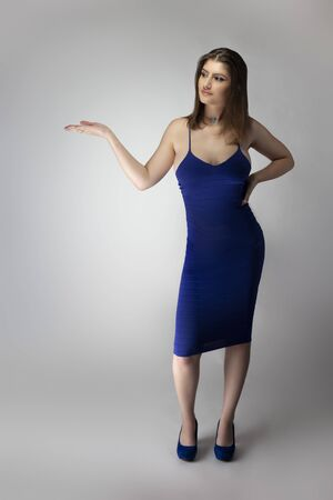 Catalog style studio shot of a Caucasian female fashion model wearing a navy or royal blue summer dress.  She is posing to show trendy style of the outfit or clothing