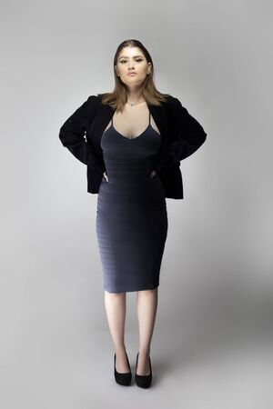 Female model posing as a business woman looking confident like a boss or a manager. Her outfit is a trendy charcoal blue dress with a business suit or jacket.