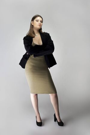 Female model posing as a sexy business woman looking confident like a boss or a manager. Her outfit is a trendy brown or tan dress with a business suit or jacket.