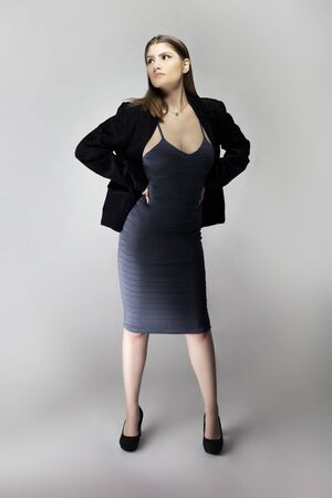 Female model posing as a business woman looking confident like a boss or a manager. Her outfit is a trendy charcoal blue dress with a business suit or jacket. Stock Photo