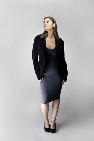 Female model posing as a sexy business woman looking confident like a boss or a manager. Her outfit is a trendy charcoal blue dress with a business suit or jacket.  Stockfoto