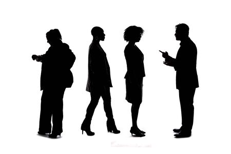 Silhouettes of a group of workers depicting a company or networking event.  The businessmen and businesswomen are unrecognizable and anonymous and represents an office team or staff.