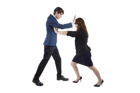 Businessman and Businesswoman pushing each other away.  Depicts social distancing or conflict among workers because of competition and lack of teamwork