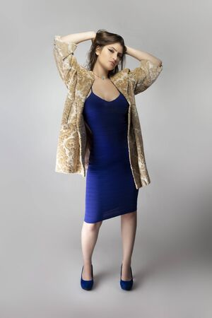 Female fashion model wearing a beige brocade wool or cotton coat and a blue sexy dress in studio catalog style.  Depicts spring or fall trends