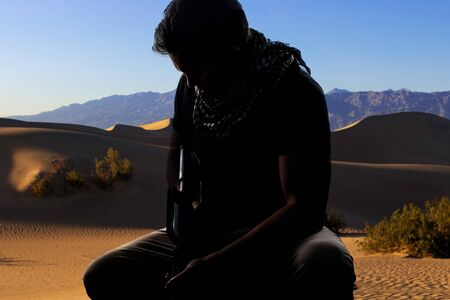Silhouette of a male soldier resting in the shade on a desert and holding a rifle.  Depicts the private military industry, militia, or special forces.  He looks tired and homesick