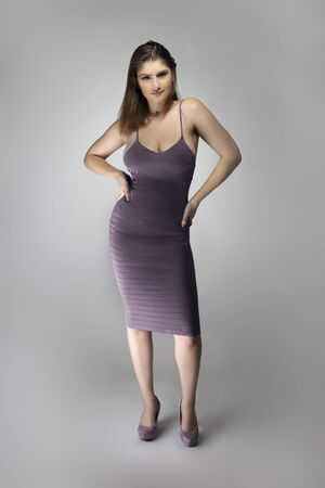 Female fashion model wearing a trendy slim fit purple, or lavender violet summer dress in a studio for summer and spring collection catalog. She is sexy and looking confident Banque d'images