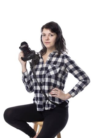 Young female art student holding a dslr camera and studying to be a professional or amateur photographer.  She looks creative and inspired to become a photo journalist