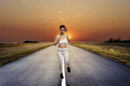 Fit woman wearing sportswear running or jogging alone on an isolated road for exercise during social distancing. She is determined to keep a healthy lifestyle