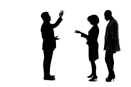 Silhouette of a group of unrecognizable people crowded together ignoring social distancing and talking to each other and socializing. They are co-workers networking or friends hanging out