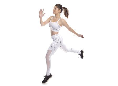 Female model wearing active wear exercising and leaping or jumping forward from a running pose. She is isolated on a white background so it can be used in composites