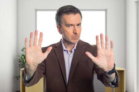 Businessman holding hands up as a stop gesture to tell co-workers to stay away and keep social distancing in the office or workplace because he is scared