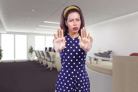 Businesswoman holding hands up as a stop gesture to tell co-workers to stay away and keep social distancing in the office or workplace because she is scared