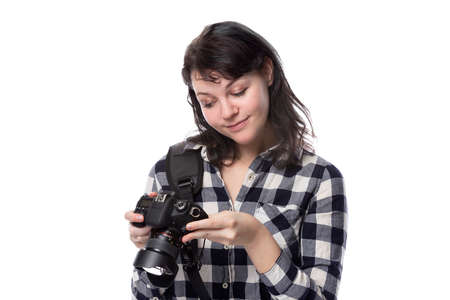 Young female freelance professional photographer or art student or photojournalist on a white background holding a camera.  She looks like she is thinking creatively