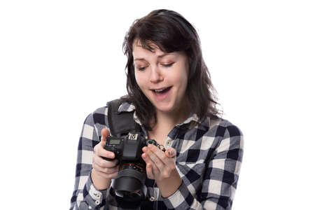Young female freelance professional photographer or art student or photojournalist on a white background holding a camera. She looks happy and successful Фото со стока