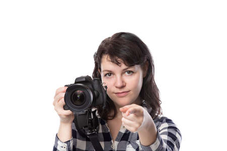 Young female freelance professional photographer or art student or photojournalist on a white background holding a camera. She is pointing forward at her client