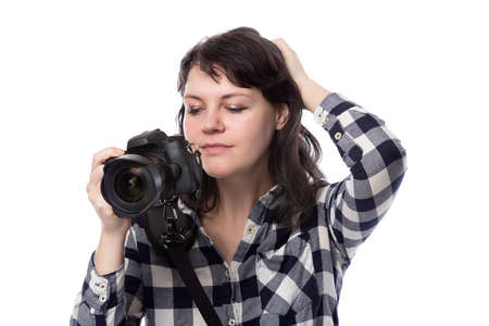 Young female freelance professional photographer or art student or photojournalist on a white background holding a camera. She looks worried of mistakes