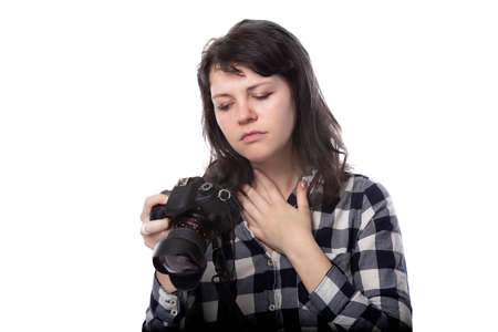 Young female freelance professional photographer or art student or photojournalist on a white background holding a camera. She is feeling sick or unwell Stock Photo