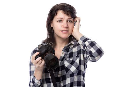Young female freelance professional photographer or art student or photojournalist on a white background holding a camera. She is confused or shy Stock Photo