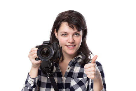 Young female freelance professional photographer or art student or photojournalist on a white background holding a camera with thumbs up Stock Photo