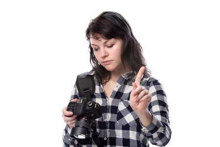 Young female freelance professional photographer or art student or photojournalist on a white background holding a camera telling client to stop