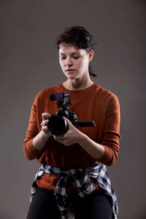 Young female photographer holding a camera in a studio. She is posed and lit so the background can be changed for composites. Shot on grey background Banque d'images
