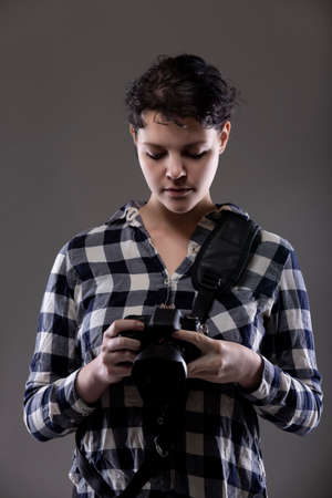 Young female photographer holding a camera in a studio. She is posed and lit so the background can be changed for composites. Shot on grey background
