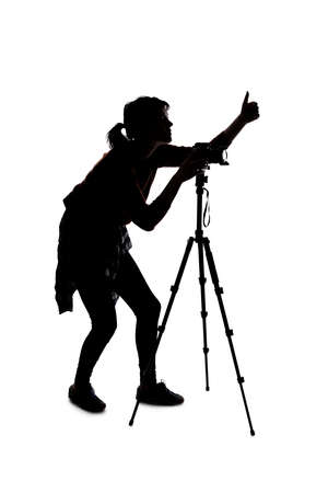 Silhouette of a photographer with a camera on a white background isolated for composites. She is posed with a thumbs up gesture