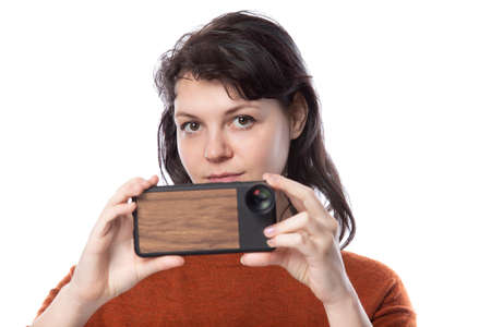 Female tourist or photographer doing mobile photography with a cell phone as an alternative equipment for hobby. The camera phone is smaller and lighter than a traditional dslr