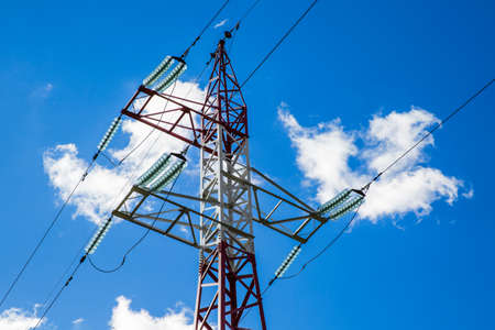 Tower of high voltage lines against the blue sky with clouds Stock Photo