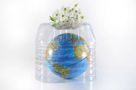 Planet earth under a plastic bottle. Global warming due to greenhouse effect. Pollution by plastic debris. Isolated white background.