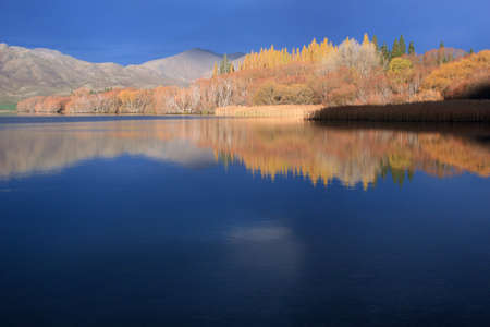 Autumn colours reflected in alpine lake photo