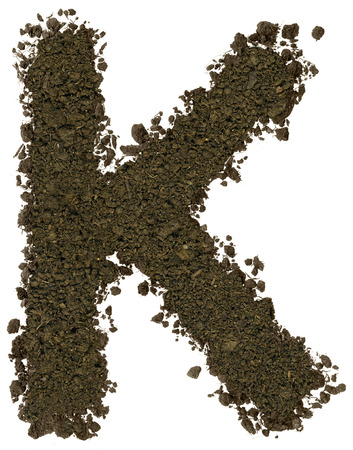 Alphabet made of brown soil on white background. High sharp and detail. Letter K