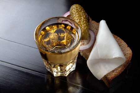Russian vodka in small glass with black bread, pickled, onion and bit of lard on white background 写真素材